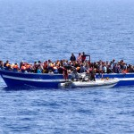 italian-navy-a-boat-filled-with-migrants-receives-aid-from-an-italian-navy-motor-boat